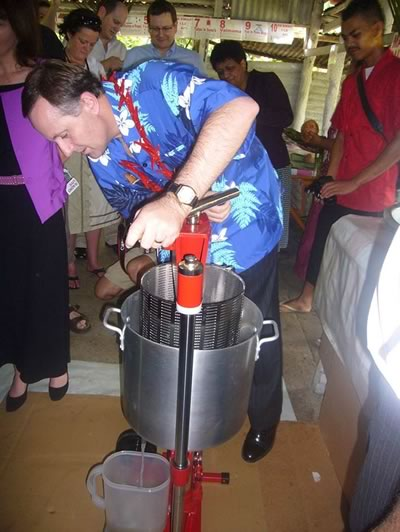 "John Key, former Prime Minister of New Zealand using the Aquarius coconut oil press while visiting Apia, Samoa in 2009. While using the press he said "" This is easier than being Prime Minister""."